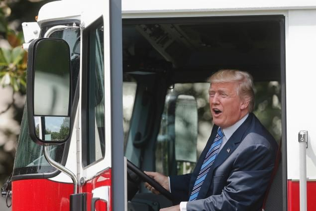 """President Donald Trump, accompanied by Vice President Mike Pence, sits inside a cabin of a firetruck during a """"Made in America,"""" product showcase featuring items created in each of the U.S. 50 states, Monday, July 17, 2017, on the South Lawn of the White House in Washington. (AP Photo/Pablo Martinez Monsivais)"""