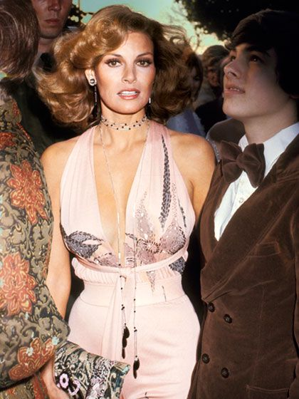 RAQUEL WELCH, 1974   The Best Oscar Looks of All Time allure.com   Iconic beauty   Big hair don't care   vintage fashion color photo print ad models magazine designer 70s does 40s 50s style retro repro halter dress hair pink print