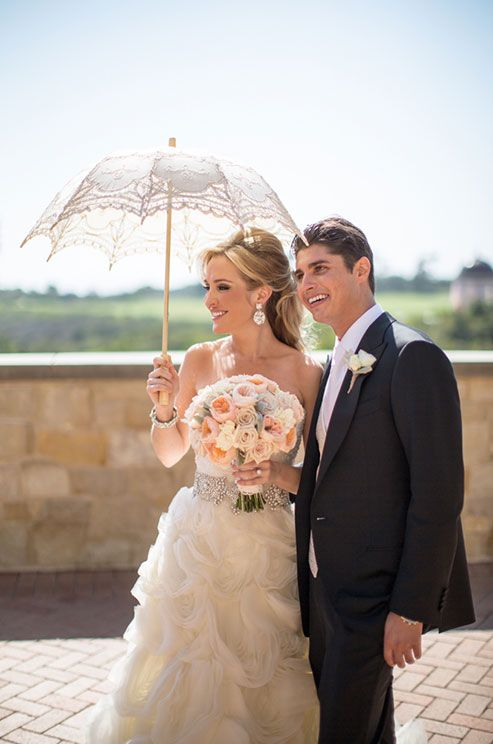 The sun-savvy bride poses with a gorgeous parasol alongside her groom-to-be.