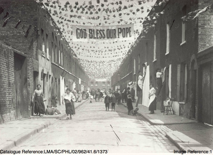 "An Irish street in Poplar: ""Rook Street, a street of tightly packed terraced houses in Poplar, east London, decorated with flags and banners for a Roman Catholic celebration in about 1914… for the appointment of the new pope, Benedict XV."" Rook St run between Poplar High Street and East India Road, where the Will Crooks Estate stands today. It was closed in 1935-9 as part of the Sophia Street Clearance Scheme by the LCC involving the demolition of nearly 200 dwellings on an area of 5.25…"