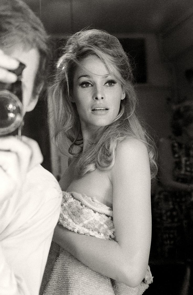 Ursula Andress wrapped in a towel on the set of 'She,' 1965. Photographer Terry O'Neill is reflected in the mirror.