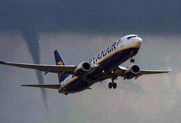 'We may be about to experience some turbulence...': Ryanair jet captured taking off in front of a TORNADO in East Midlands as Met Office issues severe weather warnings and downpours mark the end of summer