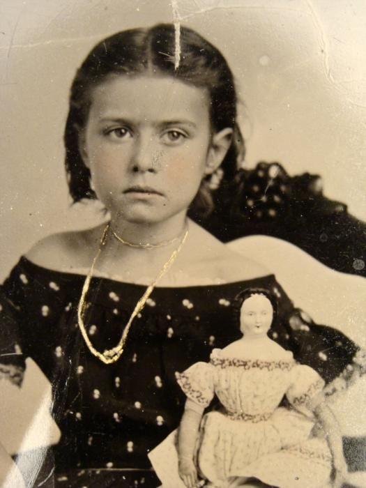 Beautiful little girl holding doll