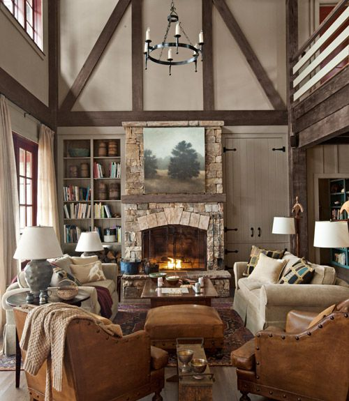 Appealingly asymmetrical built-ins—one with hidden storage, the other open—flank the great room's fieldstone fireplace in this Georgia lake house. French leather club chairs from Wyatt Childs, plus a pair of Mitchell Gold + Bob Williams sofas, serve up plenty of seating.   - CountryLiving.com
