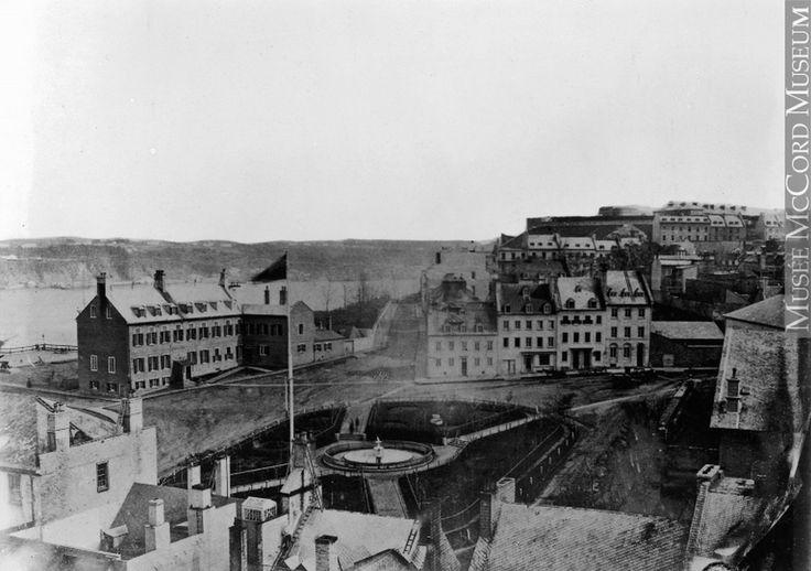 Le futur site du Château Frontenac en 1860, alors occupé en partie par l'ancien château Haldimand, devenu l'École normale Laval (Basse-ville [sic], Québec, QC, vers 1860, copie réalisée en 1929, anonyme, VIEW-24730.0, musée McCord