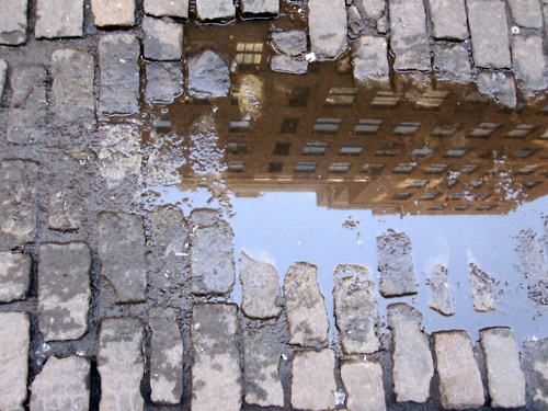Scenes of a city through a puddle