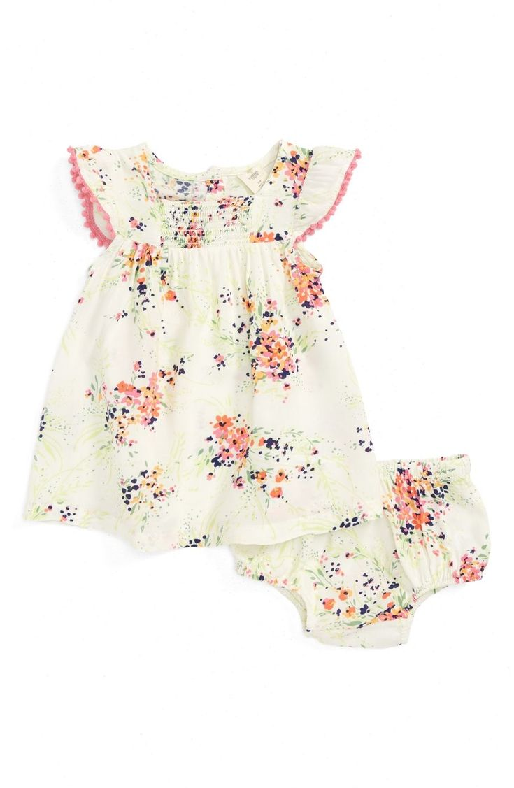 Color-pop pompoms trim the fluttering sleeves of this breezy flower-print dress with a smocked yoke for added comfort.