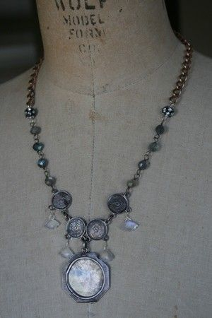 This beautiful piece has very lovely cut moonstones that remind me of snow flakes. They dangle from chain made out of old sterling coins that are dated 1904. Vintage brass watch chain connects to more moonstone gemstones and rhinestone disco balls. The pendant that hangs from the middle is half of a vintage sterling silver locket with the orginal picture of Alice. She is wearing a large Easter hat and her fine pearls. This piece measures approx.20 but if you would like it shortened please…