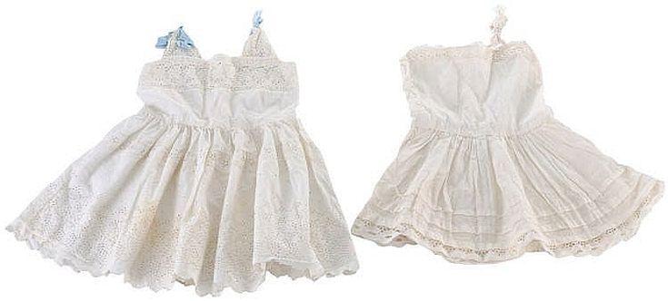 Antiguo vestido de niña en hilo de tirantas con lazo azul en raso y escote y falda decorada con bordados. Tiene pequeñas trincheras para lazada. Va con enaguas.
