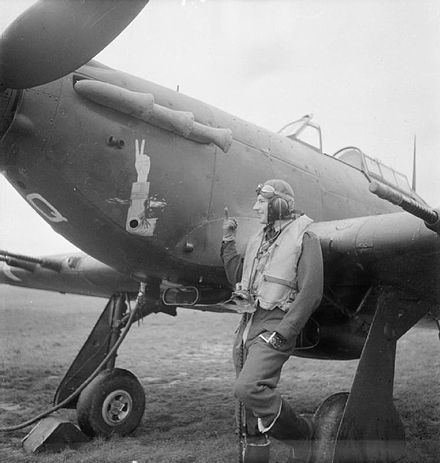 MacLachlan with his Hawker Hurricane, RAF Tangmere, November 1941. The nose art of his aircraft depicts his amputated arm giving the V sign