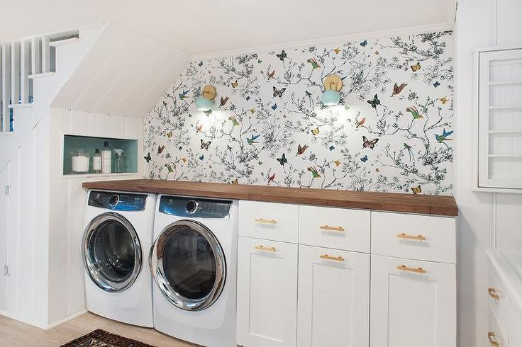 Amazing basement laundry room features a nook tucked under a staircase filled with a white front load washer and dryer and cabinets adorned with brass pulls topped with butcher block lining a wall clad in Schumacher Birds