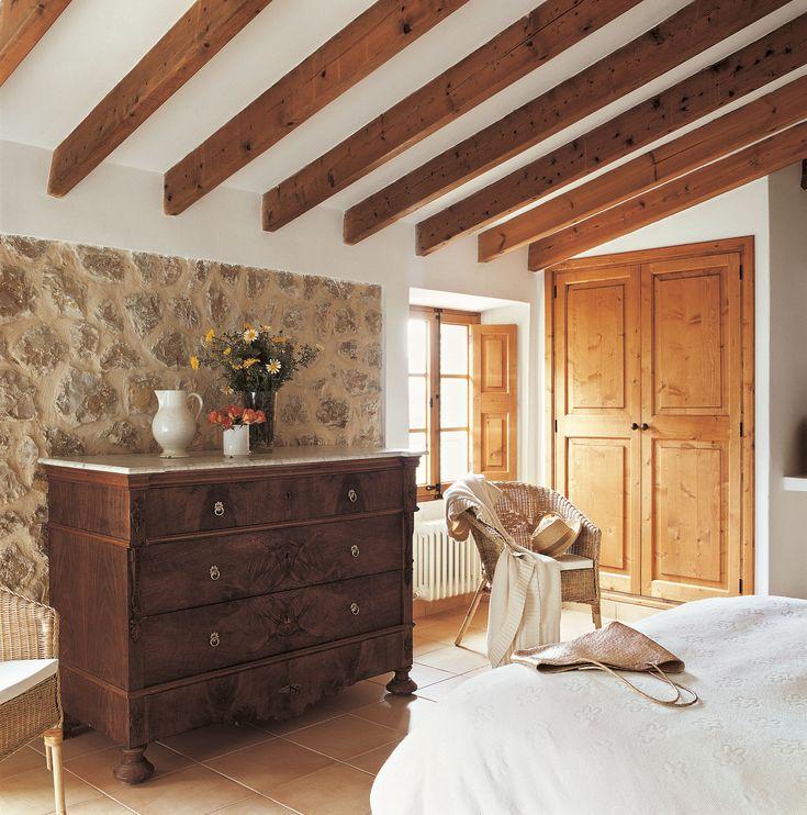 Cómoda en dormitorio rústico con pared de piedra y vigas vistas