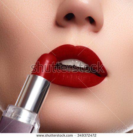 Extreme close up on model applying dark red lipstick. Makeup. Professional fashion retro make-up. dark red lipstick. Wine Lips