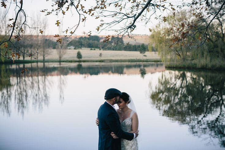 Wedding Photography with the bride and groom by the lakeside ceremony location at sunset during autumn. Taken at Bendooley Estate, Berrima, Southern Highlands, Australia - by Anthea and Lyndon Photography and Video.