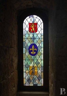 Medieval castle in Longuedoc-Roussillon, France (Provence, region of Cévennes).  Fabulous stained glass window, showing the regal lion, the fleur-de-lis, and... not sure what that last symbol is.  Winnie the Pooh?  :)  The castle dates from the 9th century and can be yours for only 2.5 million euros!