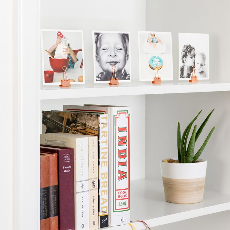 7 Square Print Display Hacks to Try at Home | Artifact Uprising Looking to switch up a shelf or countertop display? Line 'em up! Metal paper clips are the perfect stand for your Square Prints – just clip the bottom of the print and align the flat edge of the clip along your surface.