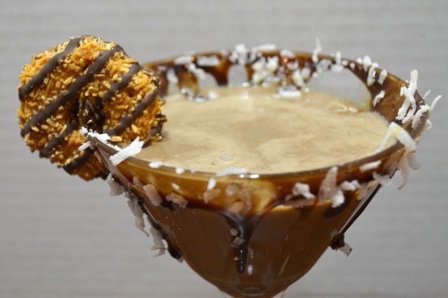 Samoa Cookie Cocktail 2 oz chocolate liqueur 1 1/2 oz caramel vodka 1 1/2 oz Malibu rum 1 oz half and half Put some chocolate syrup on a plate. Twist the edge of the glass into the syrup coating the entire rim. Then sprinkle coconut onto the glass into the syrup. Garnish with a cookie.