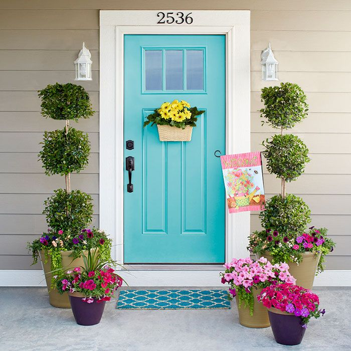 Soft touches include Eugenia topiaries standing tall over petunias, lysimachia, and verbena. Smaller pots hold dracaena, petunias, and lysimachia, while a door-mounted basket showcases gerbera daisies.