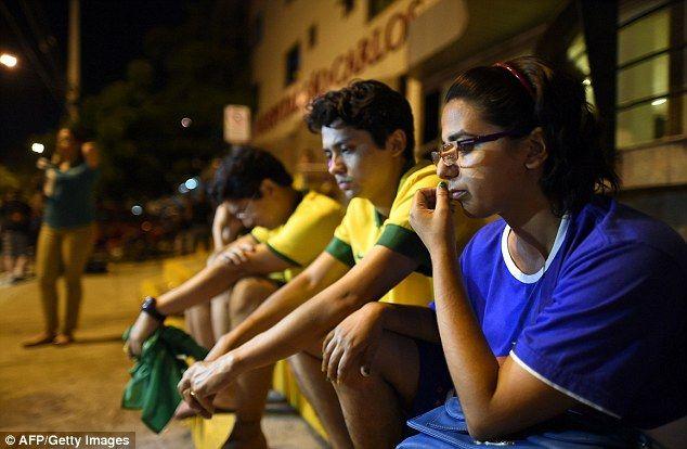 Anxious wait: Brazil fans sit outside the Sao Carlos Hospital after Neymar is taken in...