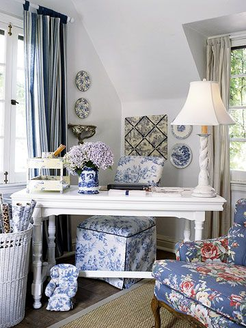 Here's a home office with character! A painted library table is used as a desk and paired with a toile-covered slipper chair in blue and white. Blue accessories on the walls and desk reinforce the theme. The windows are dressed in complementary patterns of blue stripes