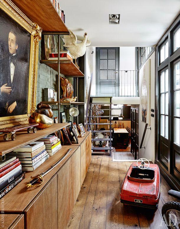 Вид из гостиной вниз, назону столовой, и наверх, на дверь спальни. Наполках у стены расставлены разные винтажные находки хозяев, от чучела гуся доскейтборда.