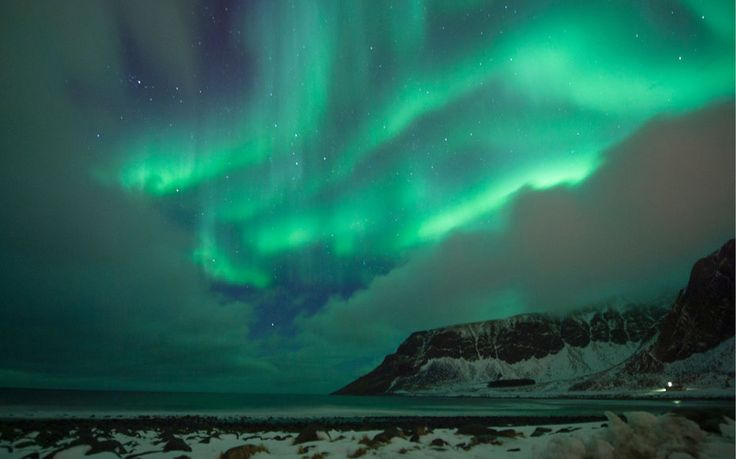 Northern lights ( aurora borealis ) illuminated the sky over the snow covered beach of Unstad, on Lofoten Island, Arctic Circle, on March 10, 2016.   Surfers from all over the world come to Lofoten island to surf in extrem conditions. Ocean temperature is