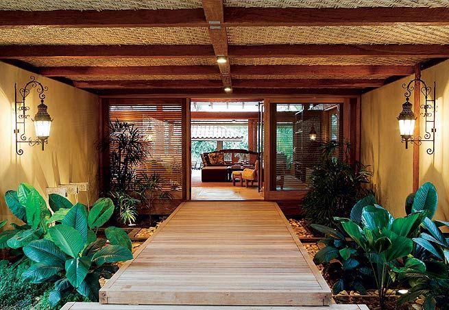 Como está a 50 cm do chão, esta casa em Catanduva, no interior de São Paulo, ganhou uma entrada flutuante, com deque de cumaru em balanço. Note que o espaço, planejado pela arquiteta Solange Cálio, é parcialmente fechado com o forro de taquara – trabalho feito com casca de bambu trançada