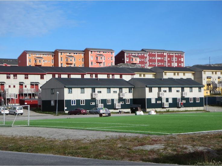A soccer field with artificial turf is surrounded by apartment buildings in the Nuussuaq district of Nuuk, Greenland.