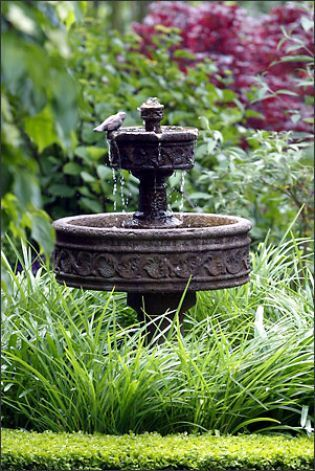 "The diminutive ""Paestum"" fountain is perfect for a small formal side garden. Here, it is surrounded by the grassy foliage of the yellow daylily 'Eenie Weenie' and dwarf blue 'Peter Pan' Agapanthus. The garden, designed by Robyn Cannon, is edged in true dwarf English boxwood. Both water features are available at Lucca Statuary. Photo: Meryl Schenker/Seattle Post-Intelligencer"