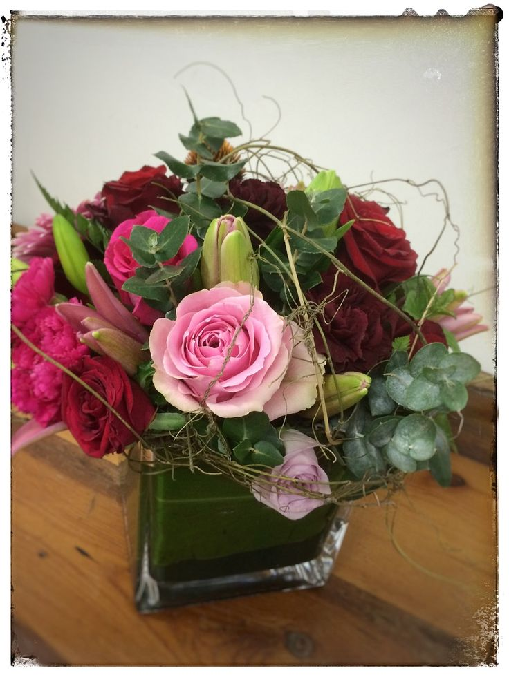 A glass vase filled with a stunning combination of pink and red flowers. A popular and recent addition to the Bloomin Box flower range. Roses, orchids, gerberas and berries add rich texture and contrast Manufacturer: Bloomin Boxes