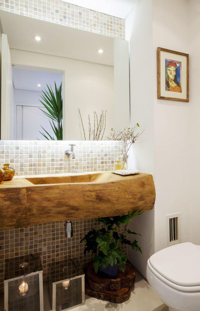 Lavabo com cuba esculpida em tora de madeira. : Banheiros rústicos por Helô Marques Associados