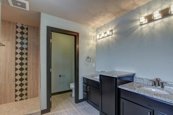 This Lovely Bathroom Features A Pair Of Vanities Separated By A Taller Vanity Base Cabinet If