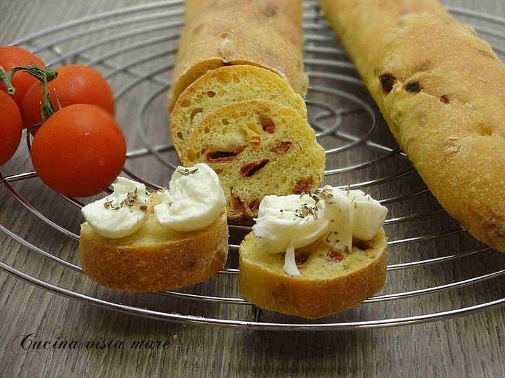 Il pane al pomodoro con pomodori secchi nell'impasto, profumato e saporito va servito con mozzarella di bufala, olio extravergine d'oliva e origano.