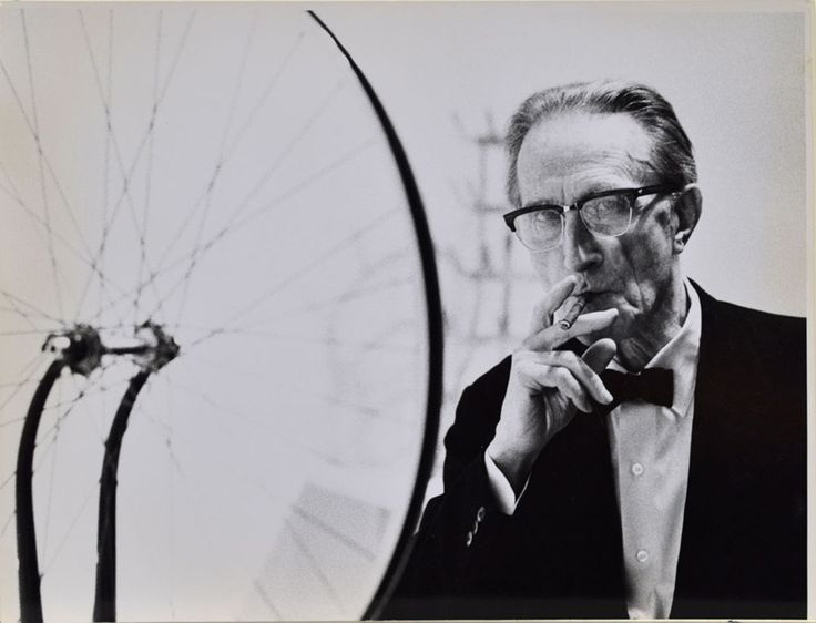 Marcel Duchamp smoking Cigar next to Bicycle Wheel, Duchamp Retrospective, Pasadena Art Museum, San Francisco 1963, vintage gelatin silver print Julian Wasser