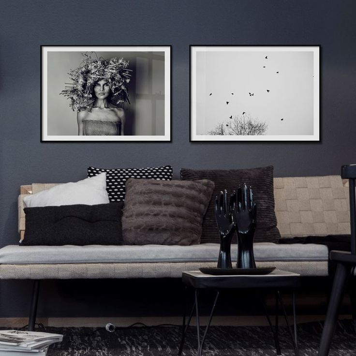 Gray living room wall with dark interior design and photo wall with framed posters from printler.com, the marketplace for photo art. Motifs by LisaLove Bäckman and Anna Höglin.