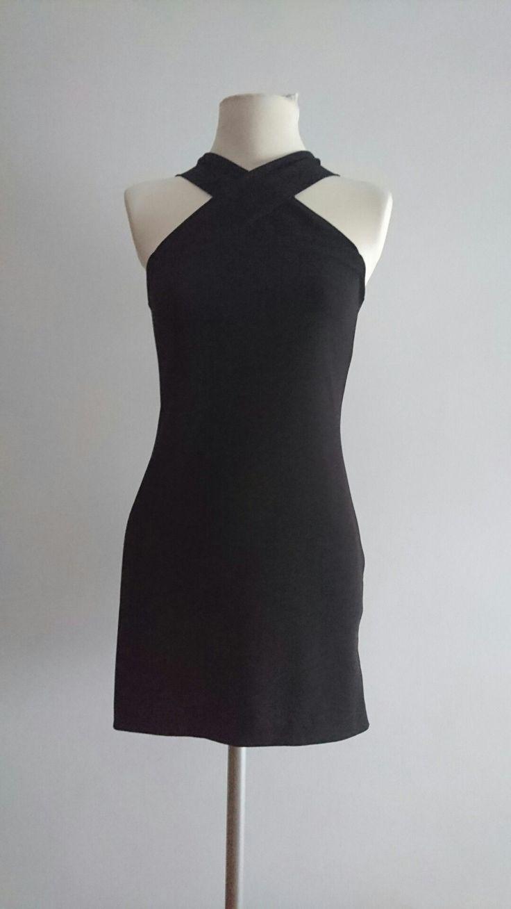 Delantero de vestido negro ajustado confeccionado en crep, con escote cruzado.