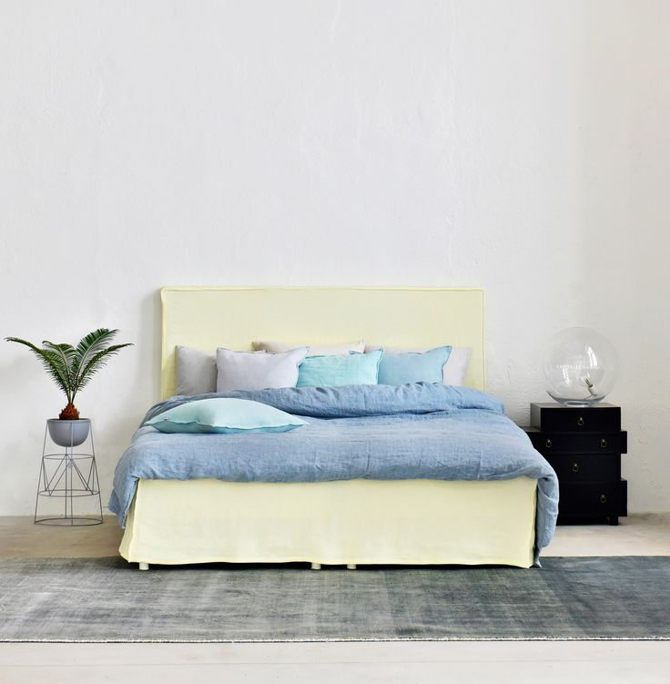 Industrial loft style apartment with huge windows   modern minimal bedroom   pastel bedroom   pale yellow headboard and bedskirt   IKEA Abelvär headboard with a Bemz cover   Did you know that Bemz offers a wide range of bedroom textiles