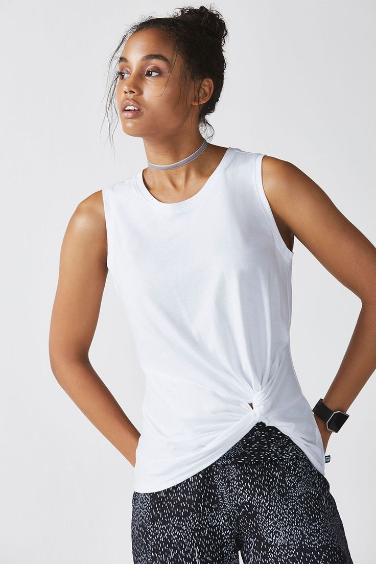 A muscle tee with a twist - literally. Transition from every activity in this feel-good tank with a knotted detail at the hem.