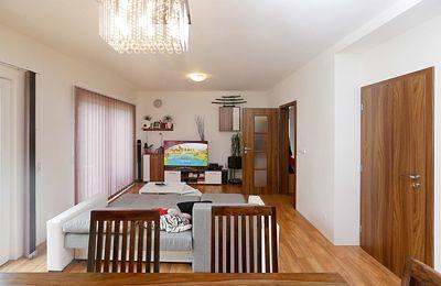 Dlažba v přízemí, která schovává podlahové topení, imituje dekor dřeva.