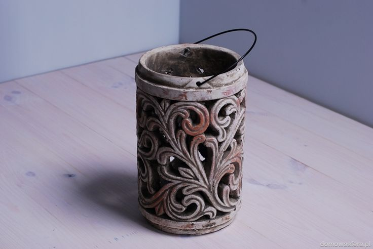 Gliniany lampion zdobiony ornamentami. Dzięki ażurowym ornamentom źródło światła rzuca z wewnątrz poszarpane cienie.