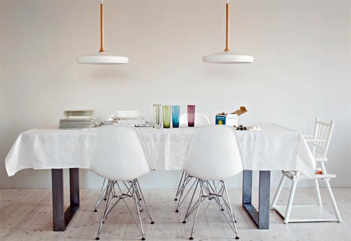 Ruokapöydän tuolit ovat Eamesin. Valkoiset Riippu-kattovalaisimet ovat Matiti Syrjälän suunnittelemat. Harri Koskisen Oma-lautaset ja värilliset Wirkkalan mehulasit ovat vain juhlakäytössä | HILLITTYÄ JUHLAA | Koti ja keittiö