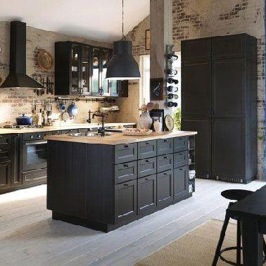 Une cuisine ouverte noire très lumineuse grâce à l'ajout de plans de travail en bois et du mur de la crédence en briques brutes vernies. Au sol, un parquet flottant gris clair fait le lien avec la salle à manger.