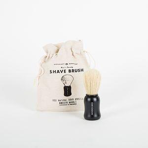 """Blaireau de rasage. Cette brosse à raser, faite à la main, en utilisant uniquement des poils de sanglier naturels pour créer une mousse épaisse lors de votre rasage. Ses poils longs et fermes exfolient légérement, massent la peau tout en créant une base idéale pour un rasage de très près. 100% Sanglier naturel, manche en bois, fait main avec imprimé blanc """"Damn Handsome"""". Fabriqué à la main au Portugal.  Men's Society"""