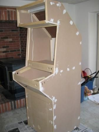 All of the screw holes were filled using wood filler and then sanded over.  They are actually invisible on the final product.    The entire cabinet was painted with two coats of heavy primer followed by two coats of Satin black acrylic.  So far the finish has held up well to heavy use and abuse.    You can also see the florescent marquee light in this picture.  I picked it up at Walmart for $3.99.
