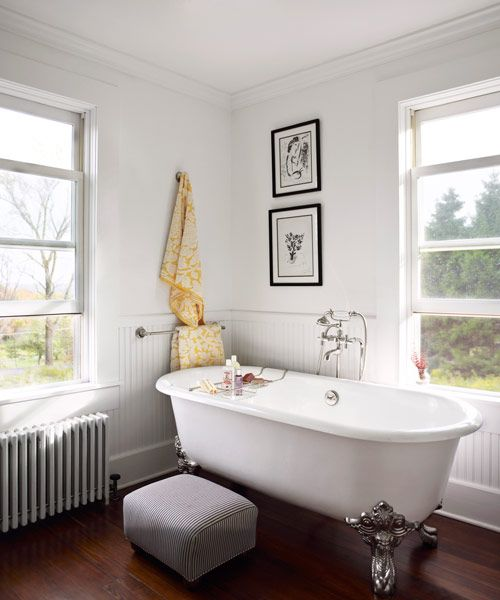 The couple converted a former studio apartment into a luxurious retreat, including this bathroom. The claw-foot tub, by Kallista, shares the space with a glass-walled shower.   - CountryLiving.com