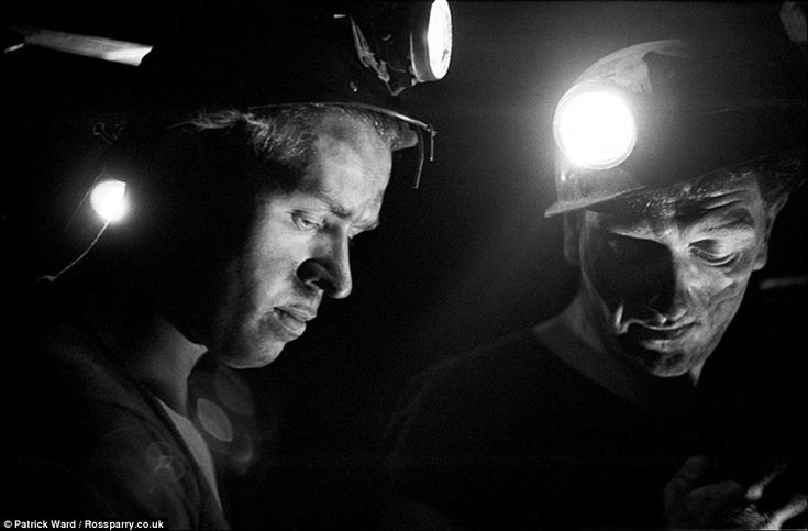 Two coal miners with their head lamps shining prepare to start their shift and get ready to enter the lift cage to go underground at Horden Colliery, County Durham in 1966. The miners endured harsh conditions working below ground extracting coal