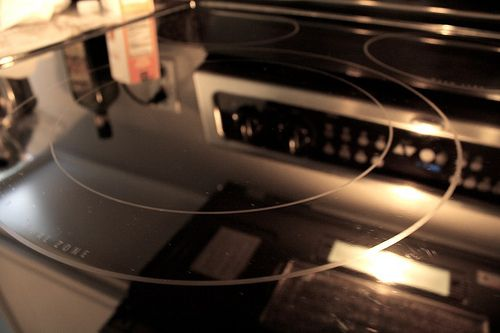 clean the glass cooktop with hot water, dish soap, baking soda, cleaning rag, gloves