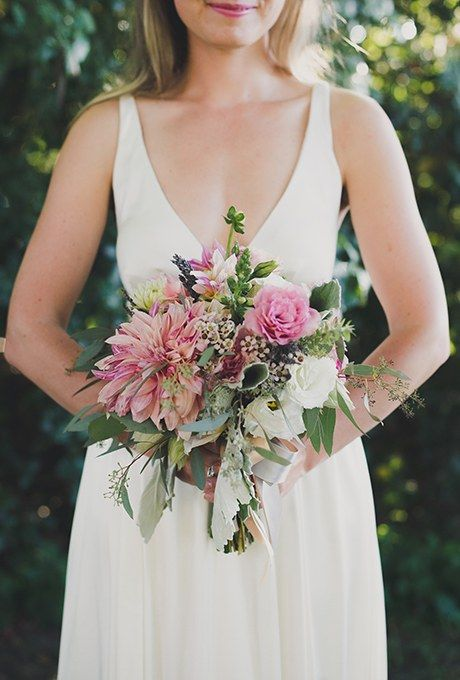 Although Amber and Cameron's Vancouver, Canada wedding was all about nautical charm, the bride decided to go her own way when it came to the bouquet. Olla Flowers created a vintage-inspired arrangement of dahlias, roses, and eucalyptus seed for Amber to carry down the aisle, but tied it back to the couple's theme with preppy buttons that secured ribbon to the handle.