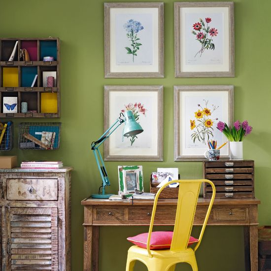 Green home office with botanical prints on wall, wooden desk and chair, open cupboard and console table.