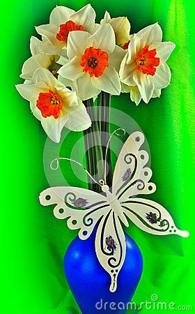 A closeup of daffodils in a vase tin butterfly decoration